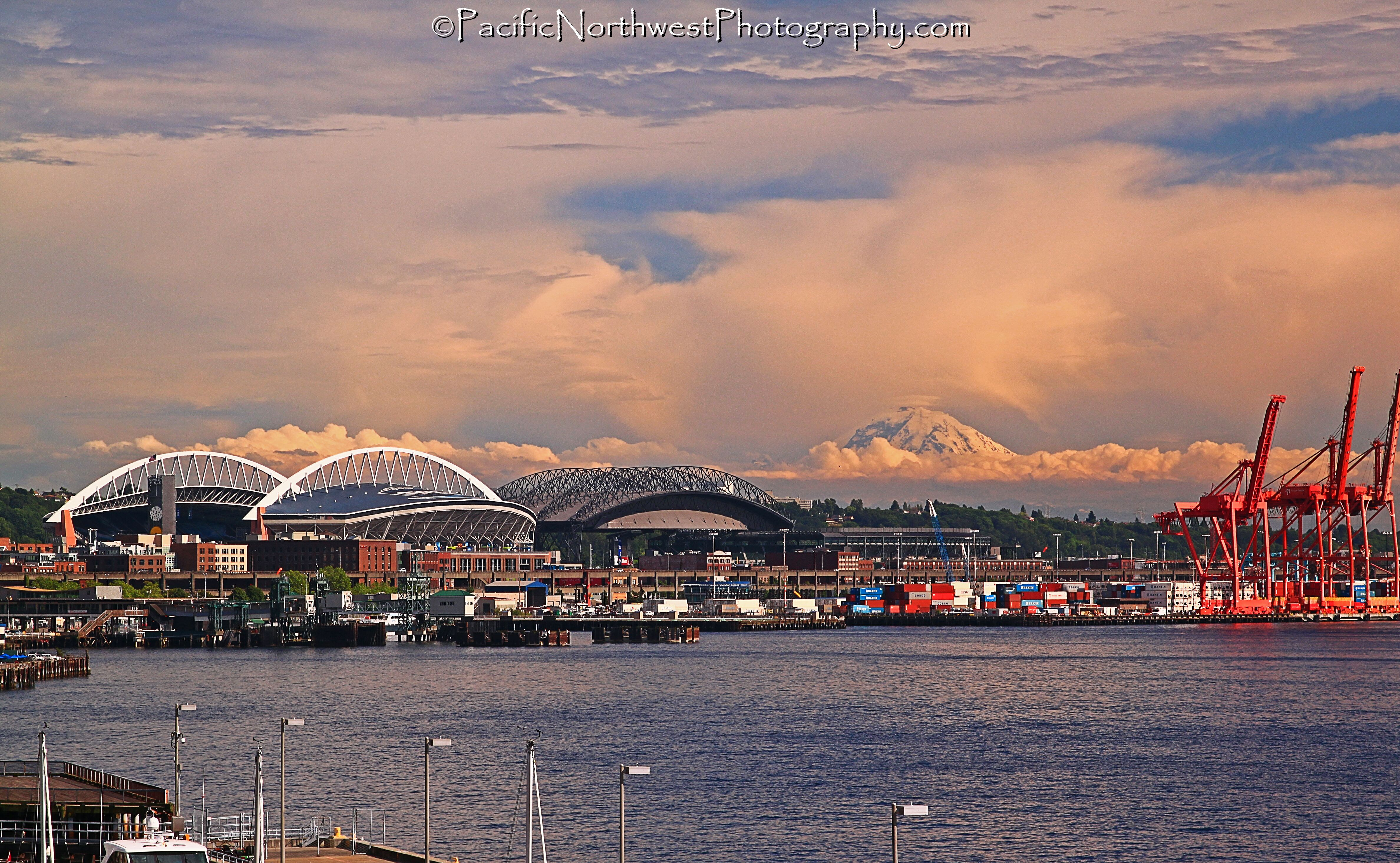 City, stadium, water, cranes, clouds and mountain